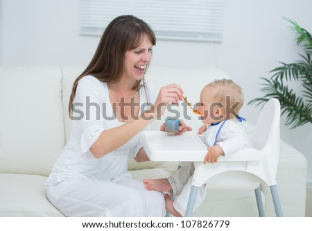 Mother sitting in a sofa while feeding a baby in living room