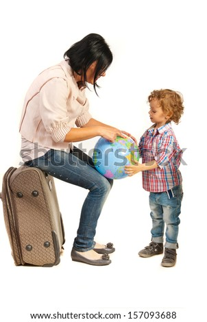Mother sitting on baggage and showing to his son destination on a world globe - stock photo