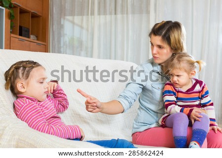 Mother sitting on sofa and scolding little daughter - stock photo