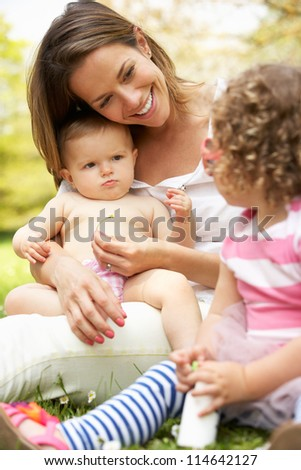 Mother Sitting With Daughters In Field Of Summer Flowers
