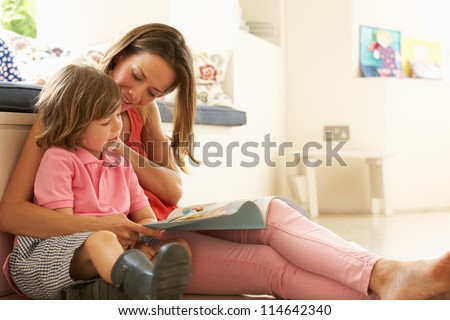 Mother Sitting With Son Reading Story Indoors - stock photo