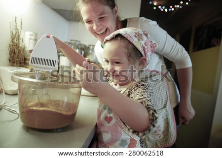 Mother smiling and tutoring her daughter in the kitchen as she is preparing dough for homemade Christmas cake. Family values, inclusion, learning through experience concept.  - stock photo