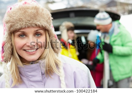 Mother Smiling At Camera Whilst Family Load Skis In Boot Of Car - stock photo