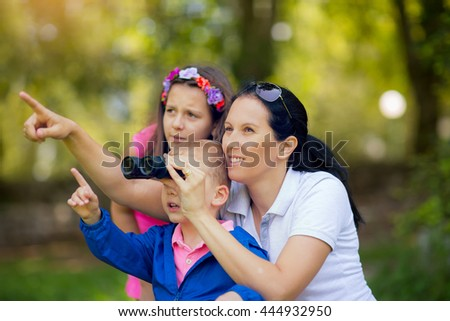 Mother son and daughter exploring the environment with a binocular - stock photo