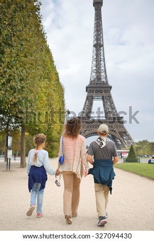 Mother, son and daughter walk in the park near the Eiffel Tower in Paris, view from the back - stock photo