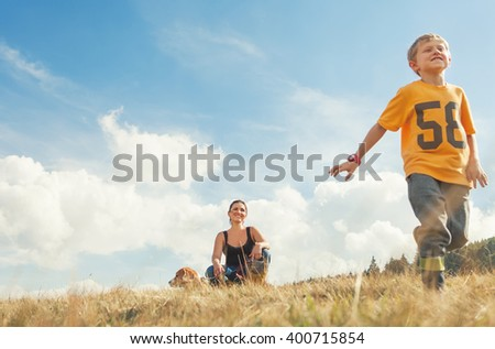 Mother son and dog on the golden field - stock photo