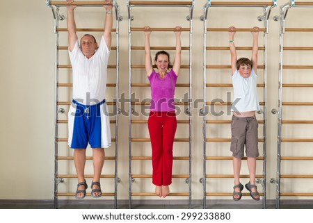 mother son and grandfather hanging on a horizontal bar in a gym - stock photo