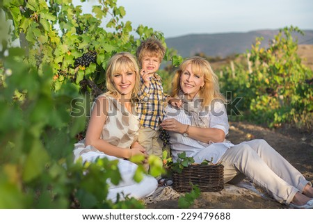 Mother, son and grandmother sitting to the vineyard. - stock photo