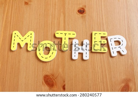 MOTHER, spell by woody puzzle letters with woody background
