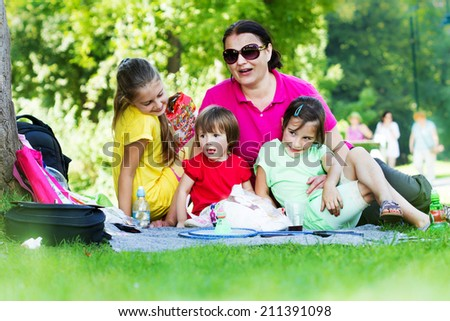 Mother spending a nice time with her children on a picnic - stock photo