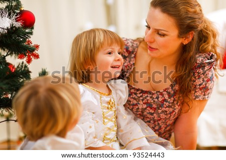 Mother spending time with daughters near Christmas tree