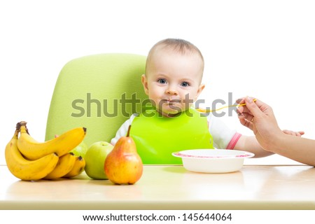 mother spoon feeding baby girl - stock photo