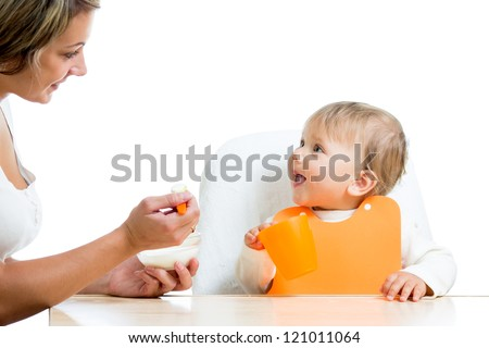 mother spoon feeding her baby girl - stock photo