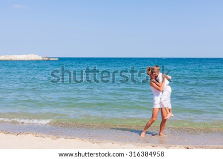 Mother standing with her son on the sea beach