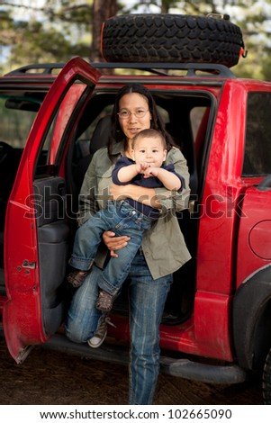 Mother stepping out of the back seat of a car with a baby. Shallow DOF, boy's face in focus. - stock photo