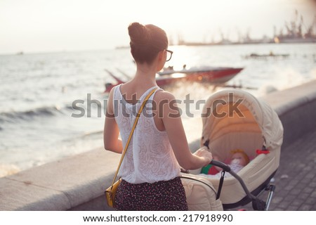 Mother strolling with newborn - stock photo