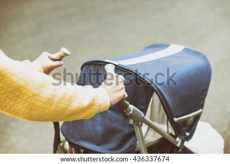 Mother strolling with newborn in carriage. Closeup shot