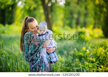 mother strong embraces the newborn son, walk in the beautiful park, together smile