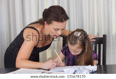 Mother studying with her daughter at the table - stock photo