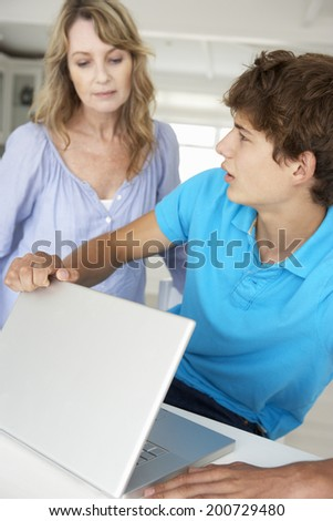 Mother supervising teenage son using laptop - stock photo