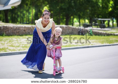Mother supports the little daughter who learns to ride the scooter in the park in summer sunny day - stock photo