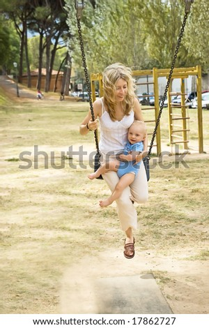 Mother swinging with baby