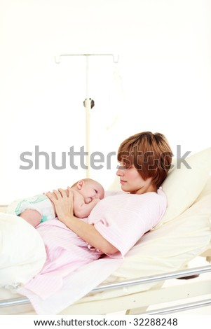 Mother taking care of her newborn baby in hospital with copy-space - stock photo