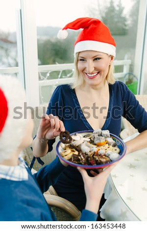 Mother taking Christmas Cookies from her Son - stock photo