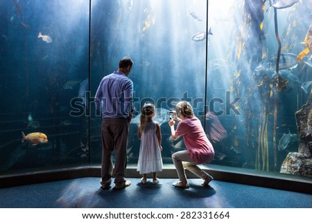 Mother taking photo of fish while daughter and father looking at fish tank at the aquarium - stock photo
