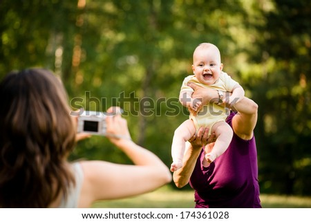 Mother taking photo of grandmother holding her granddaughter - outdoor in nature - stock photo