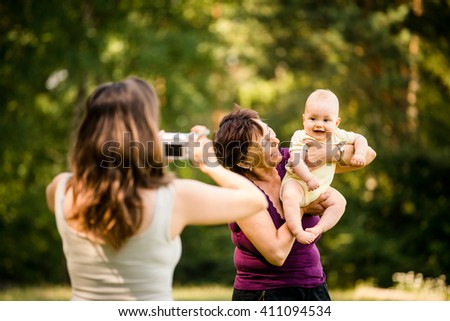 Mother taking photo of grandmother holding her granddaughter - outdoor in nature