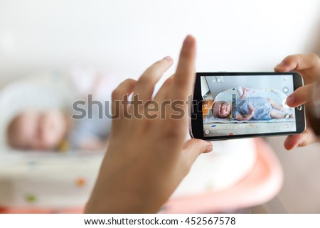 Mother taking photos of a baby girl with her mobile phone.