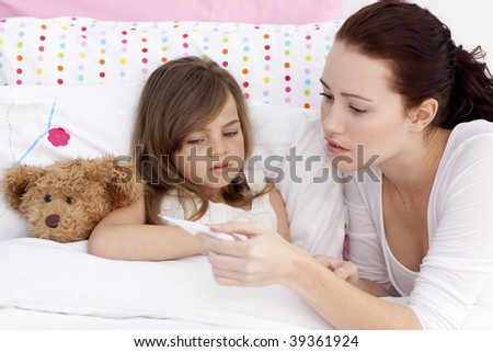 Mother taking sick daughter's temperature in bed