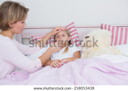 Mother taking the temperature of sick daughter at home in the bedroom - stock photo