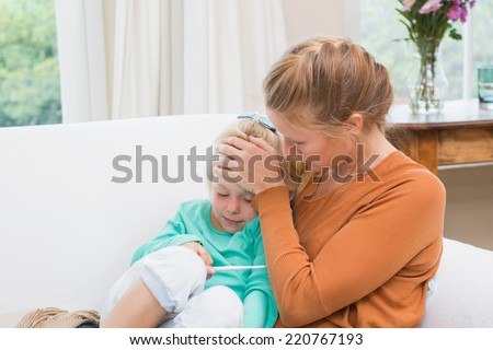 Mother taking the temperature of sick daughter at home in the living room