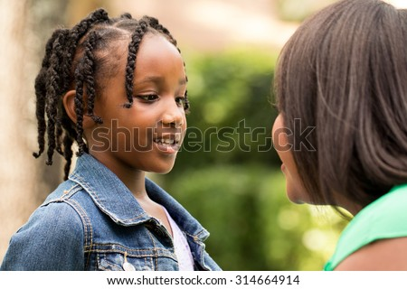 Mother talking with her daughter. - stock photo