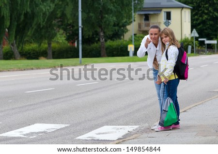 Mother teach daughter about safety rules before crossing the street on the school way - stock photo