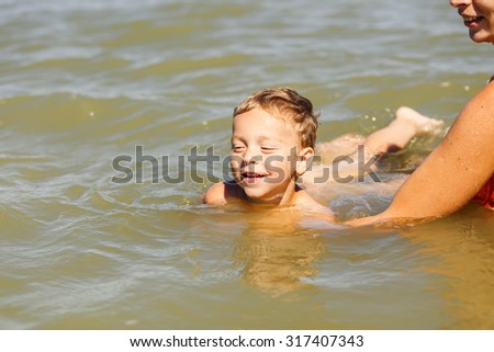 mother teach her son to swim in lake