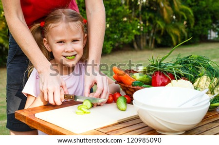 mother teaches daughter  knife cut cucumber - stock photo