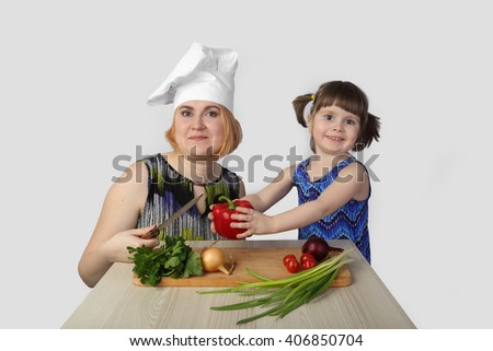Mother teaches daughter to cook on gray background - stock photo