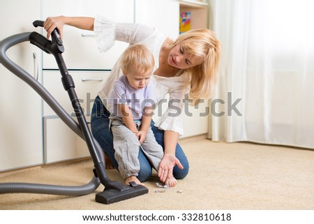 Mother teaches her child son room cleaning with vacuun cleaner