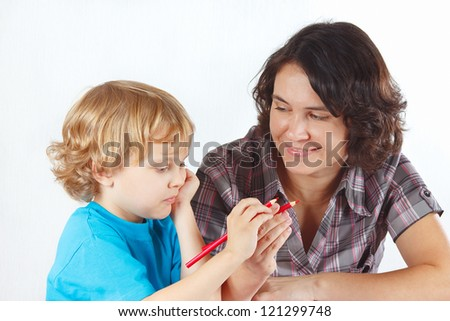 Mother teaches her child to draw with color pencils on a white background - stock photo
