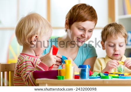 mother teaches her children to work with colorful play clay toys - stock photo
