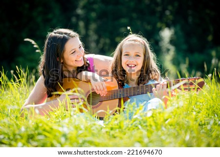 Mother teaches plaing guitar her child - outdoor in nature on sunny day - stock photo
