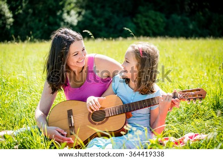 Mother teaches playing guitar her child - outdoor in nature on sunny day - stock photo