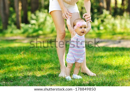 Mother teaching baby to walk in the park - stock photo