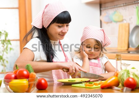 Mother teaching child girl making salad in kitchen. Mom and kid chopping vegetable on cutting board with knife. Cooking concept of happy family preparing food for dinner.