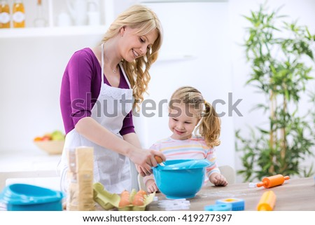Mother teaching child how to break an egg
