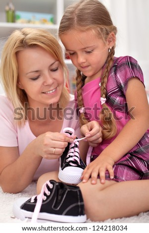 Mother teaching child how to tie shoes - showing the steps - stock photo