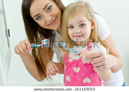 Mother teaching cute baby how to brush teeth with toothbrush - stock photo